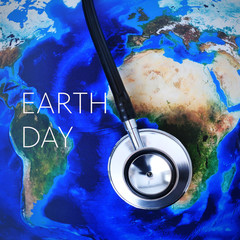 stethoscope on a world map (furnished by NASA) and the text eart
