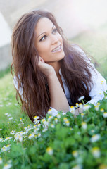 Brunette girl with brackets lying on the grass with many flowers