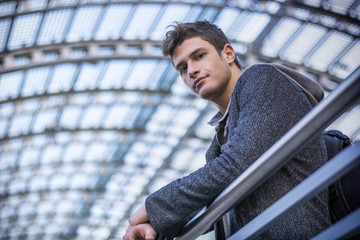 Attractive young man inside modern building, station or airport