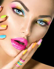 Beauty girl face with vivid makeup and colorful nail polish