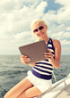 smiling woman sitting on yacht with tablet pc