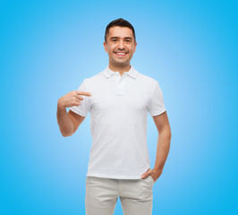 smiling man in t-shirt pointing finger on himself