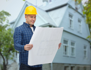 smiling builder with blueprint over house