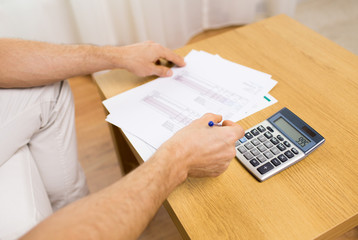 close up of man with papers and calculator at home