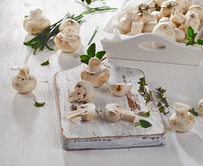 Fresh whole white button mushrooms  on  wooden cutting board.