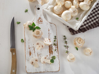 Fresh white button mushrooms  on a wooden board.