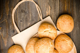 Homemade buns and paper bag on wooden background