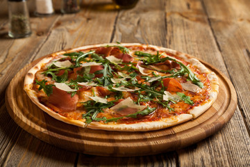 """Italian pizza """"Parma"""" on a wooden table."""