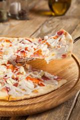 "Italian pizza ""Caesar"" on a wooden table."