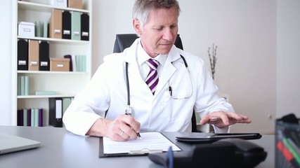Doctor or practitioner using digital tablet while writing notes