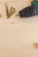 Electric screwdriver and some screws on a wooden background