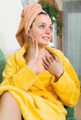 Girl applying cream on skin