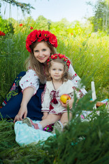 Mom and daughter in traditional Ukrainian costume in the forest