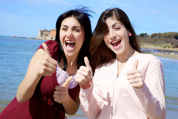 Happy smiling young women in front of the sea thumb up