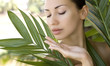 Beautiful woman holding aloe vera gel, skin care and wellness. F