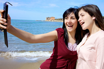 Two happy young women taking selfie smiling on the beach