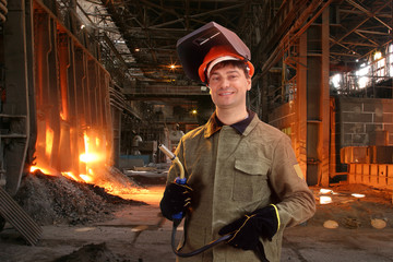 Portrait of a happy male welder standing against the foundry