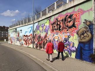 Rentner spazieren an Graffiti Wand