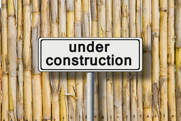 Under construction written on road sign against a bamboo fence