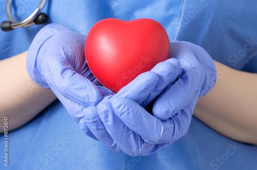 Leinwanddruck Bild Doctor holding a heart