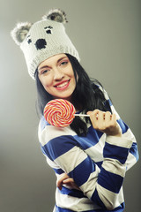 woman with winter hat holding big lollipop