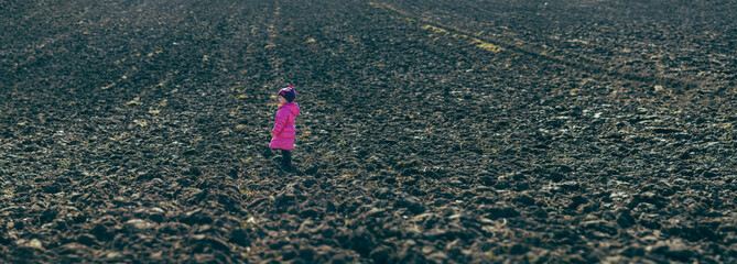 baby girl standing in the midst of plowed fields.