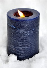 blue candle in the snow