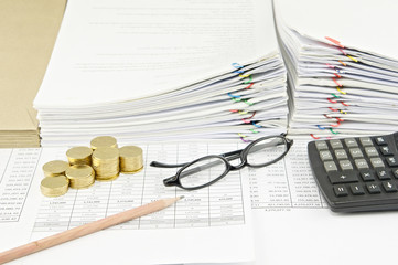 Brown pencil and gold coins with spectacles and calculator