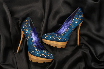 High-heeled shoes  lying on black  fabric