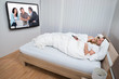 Couple In Bed Watching Television