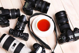 Fototapety Modern cameras with cup of tea  on wooden table, closeup