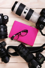 Modern cameras with glasses and pink diary