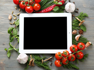 Digital tablet with fresh herbs, tomatoes and spices