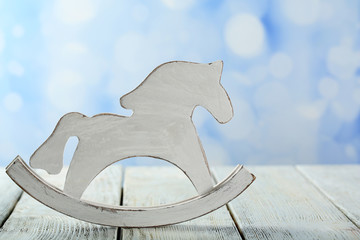 Decorative rocking horse on wooden table, on light background