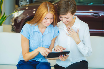 two women are talking during work day in office