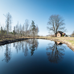 reflections of country house in the pond