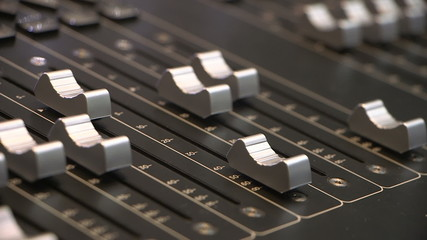 Audio engineer adjusting faders