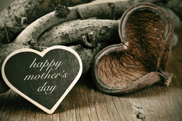 happy mothers day in a heart-shaped chalkboard on a rustic backg