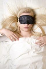 Beautiful young woman sleeping with eye mask