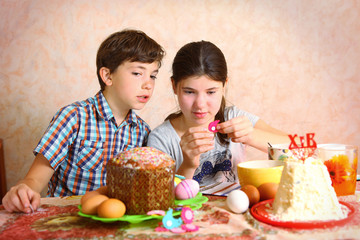 siblings brother and sister decorate egg and easter cake for eas