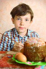 preteen handsome boy decorate easter egg and cake