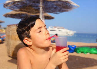 preteen handsome boy drink cocktail on the seaside beach