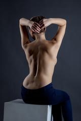 Rear view of seminude model posing in studio