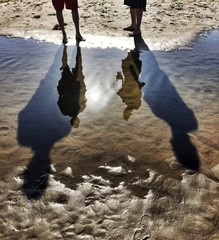 Reflections And Tall Shadows Of Two People At The Beach