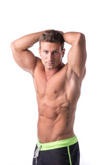 Muscular young bodybuilder striking a pose. Isolated