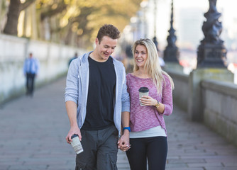 Young couple walking in London holding a cup of tea