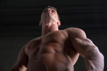 Low angle shot of shirtless male bodybuilder on dark background