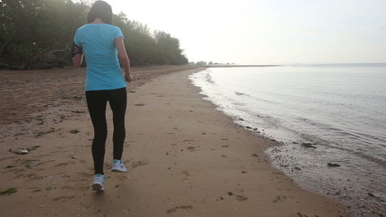 young european girl goes at jog trot along beach at sunrise