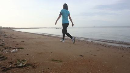 young european girl goes at jog trot along beach at sunrise
