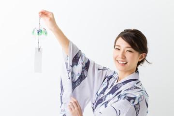 浴衣を着て風鈴を持つ女性